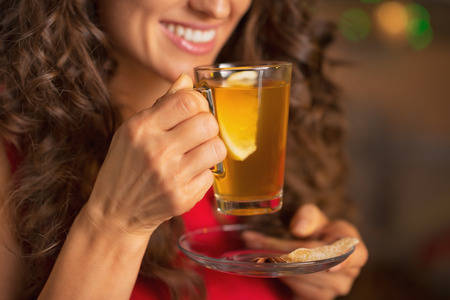 Closeup on happy young woman drinking ginger tea with lemon Stock Photo - 22887728