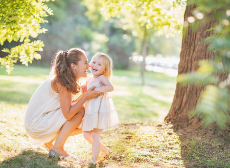 off day: Portrait of happy mother and baby playing outdoors Stock Photo