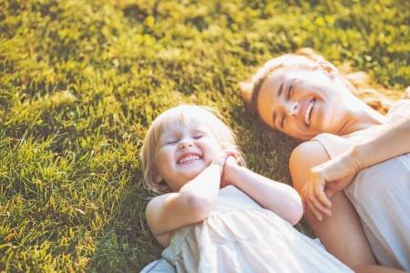 풀밭에 누워 웃는 어머니와 아기 스톡 콘텐츠 - 22876498
