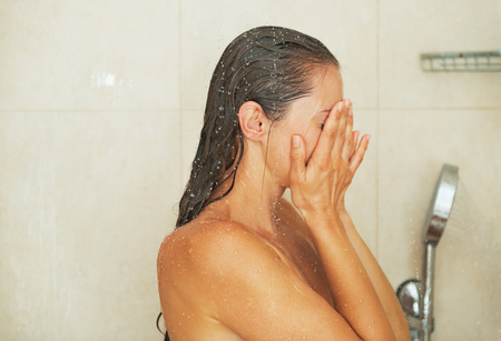 Woman closing face with hands in shower photo