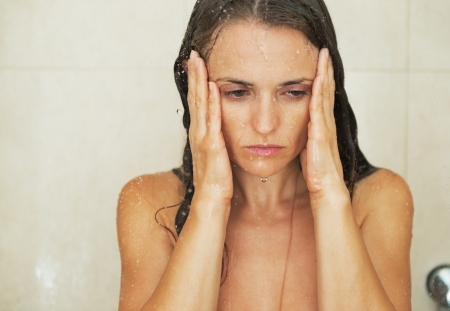 Portrait of stressed young woman in shower photo