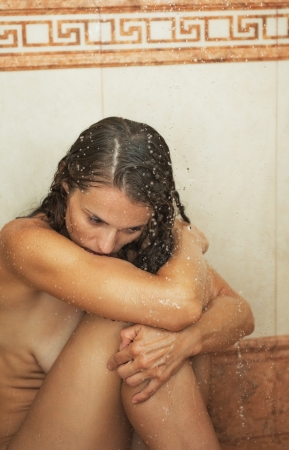Frustrated young woman sitting in shower photo