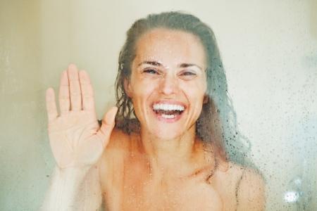 Sonriente mujer joven mirando a través del vidrio que llora en la ducha