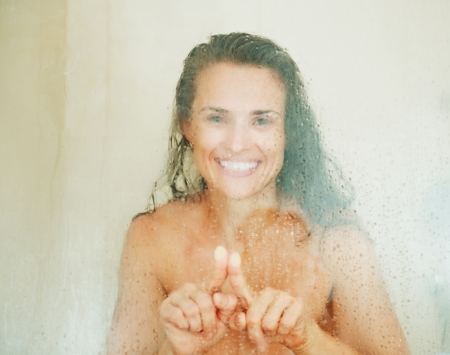 Happy young woman drawing heart in weeping glass shower door Stock Photo