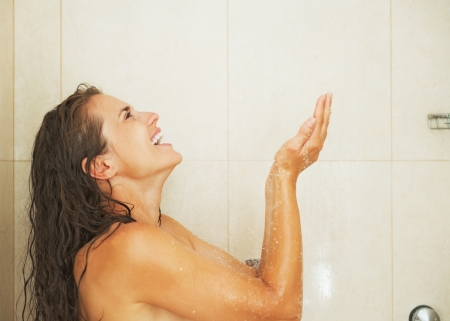Smiling young woman catching water drops in shower Stock Photo