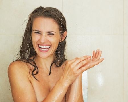 cabine de douche: Portrait de jeune femme souriante de prendre une douche