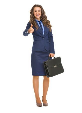 Full length portrait of smiling business woman with briefcase showing thumbs up photo