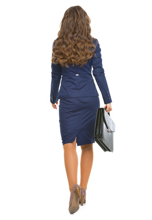 anonym: Full length portrait of business woman with briefcase going straight . rear view