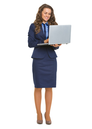 topicality: Full length portrait of smiling business woman with laptop