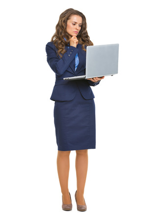 topicality: Full length portrait of thoughtful business woman with laptop