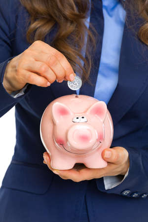 Closeup on business woman putting coin into piggy bank Stock Photo - 22887797