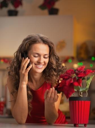 traje de gala: Sonriente joven ama de casa que habla el teléfono y jugando con la Navidad se levantó