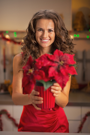 Happy young woman in red dress holding christmas rose in christmas decorated kitchen photo