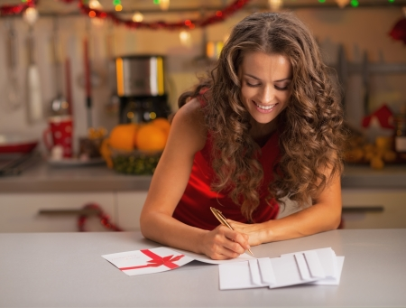 Happy young housewife signing christmas postcards in kitchen photo