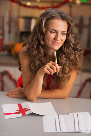 Thoughtful young housewife signing christmas postcards in kitchen photo