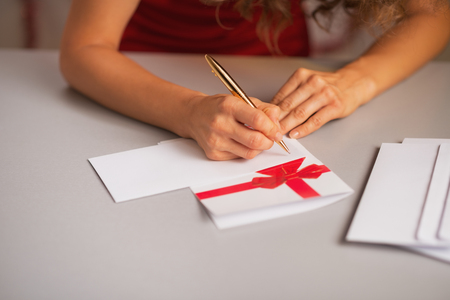 Closeup on woman writing on christmas letter in kitchen photo
