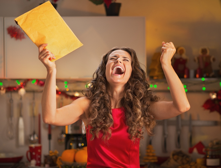 Happy young housewife with christmas package rejoicing
