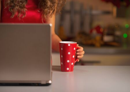 Closeup on cup of hot chocolate and woman in red dress usign laptop Stock Photo - 22887883