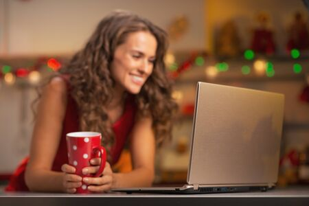 Closeup on laptop and happy young woman with cup of hot chocolate in christmas decorated kitchen Stock Photo - 22887885