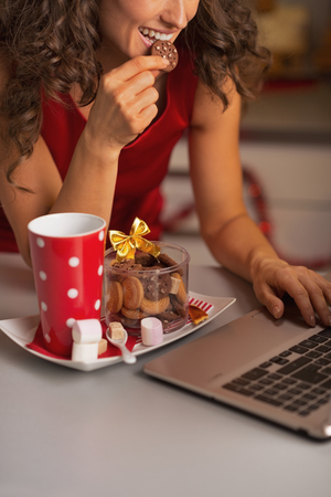 Closeup on happy woman having christmas cookies with cup of hot chocolate and usign laptop Stock Photo - 22887888