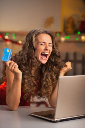 Happy young woman with credit card and laptop rejoicing Stock Photo - 22887895