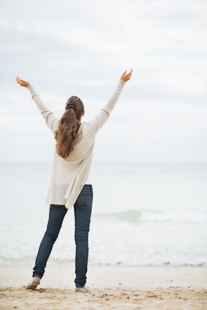 Full length portrait of happy young woman in sweater rejoicing on beach . rear view