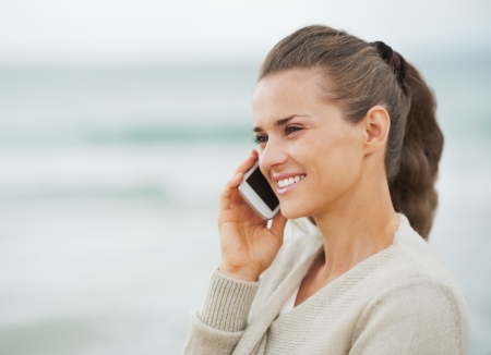 Smiling young woman in sweater on beach talking cell phone photo