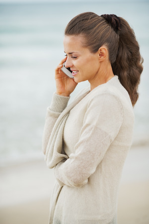 Happy young woman in sweater on beach talking mobile phone photo