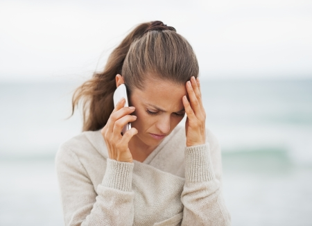 Talking on the phone: Frustrated young woman in sweater on beach talking cell phone Stock Photo