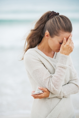 Stressed young woman in sweater on beach with mobile phone Stock Photo - 22972273