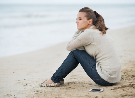 Young woman in sweater with cell phone sitting on lonely beach and looking into distance