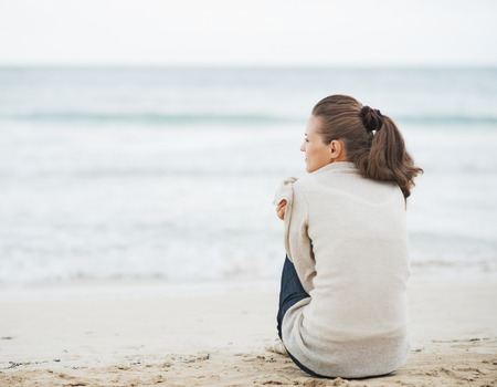 beach wrap: Young woman wrapping in sweater while sitting on lonely beach Stock Photo