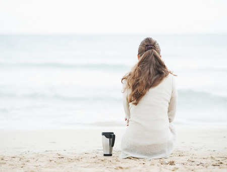 anonym: Cup of hot beverage near young woman in sweater sitting on lonely beach   rear view Stock Photo