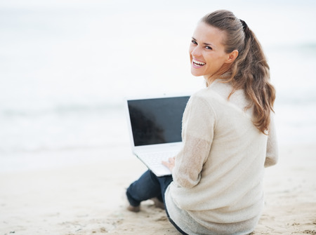 Smiling young woman in sweater sitting on lonely beach and using laptop photo