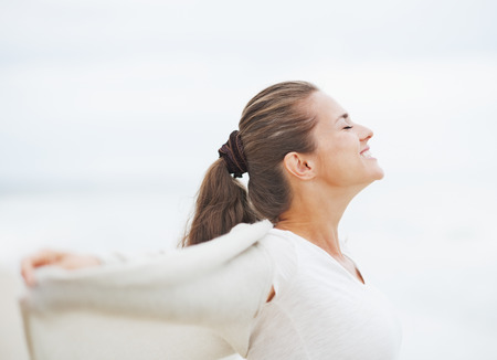 Happy young woman in sweater on lonely beach rejoicing