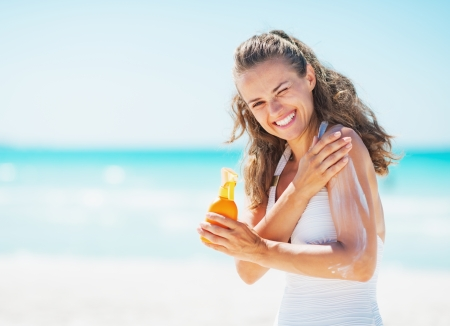 moisten: Smiling young woman applying sun block creme on beach