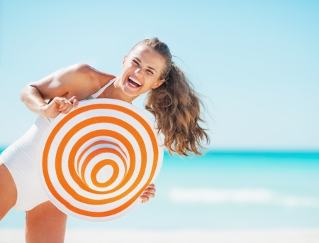 Portrait of happy young woman in swimsuit with beach hat having fun time on beach Stock Photo