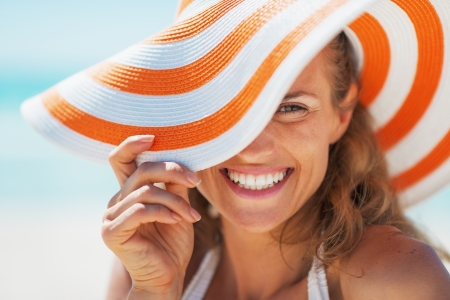 Portrait of happy young woman in swimsuit and beach hat Stock fotó
