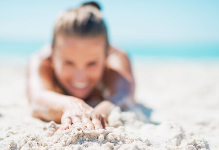 Closeup on happy young woman in swimsuit laying on sandy beach Stock Photo - 22972492