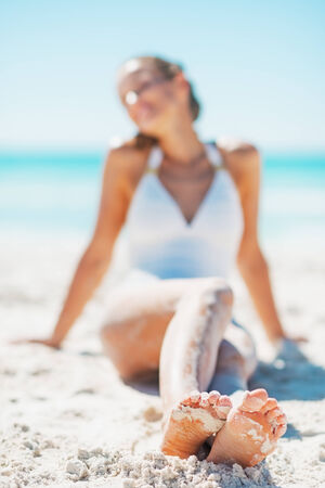 Closeup on legs of young woman in swimsuit sitting on beach Stock Photo - 22972534