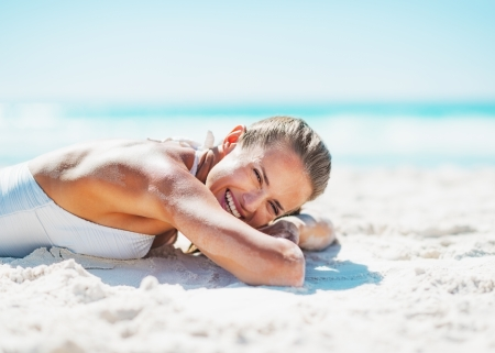 Happy young woman in swimsuit laying on sandy beach photo