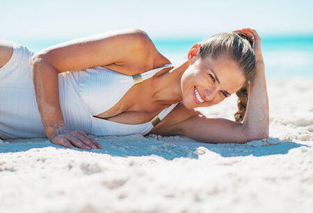 Portrait of smiling young woman in swimsuit laying on beach photo