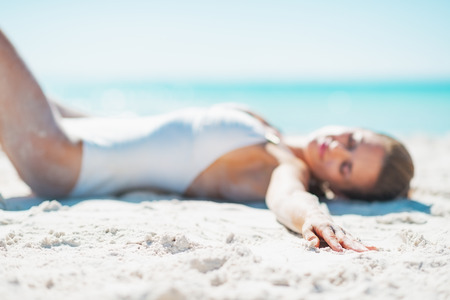 Closeup on relaxed young woman in swimsuit sunbathing on sandy beach Stock Photo - 22972550