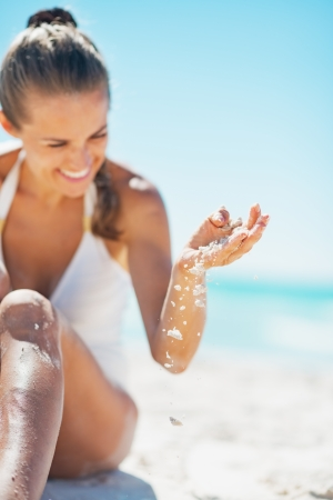 Closeup on happy young woman in swimsuit sitting on beach and playing with sand photo