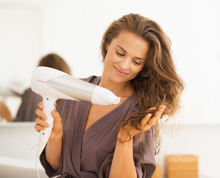 Gelukkige jonge vrouw föhnen haar in de badkamer