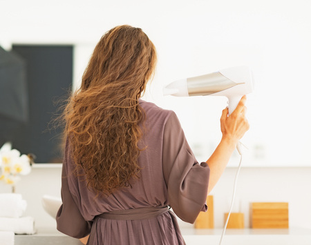 Young woman blow drying hair in bathroom . rear view photo