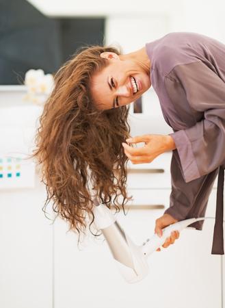 浴室で若い女性ブロー乾燥髪を笑顔