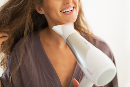 Closeup on happy woman blow drying hair photo