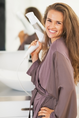 blow dryer: Portrait of smiling young woman with blow dryer in bathroom