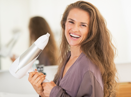 blow dryer: Smiling young woman holding blow dryer